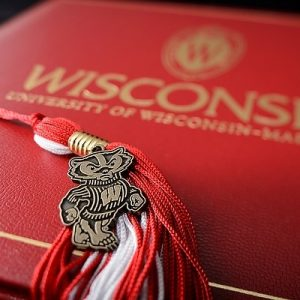 A graduation tassel with a pendant of mascot Bucky Badger is pictured with a University of Wisconsin-Madison diploma cover on May 1,