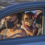 Mom and daughter in car viewed through driver window, both wearing masks to protect against COVID-19