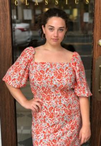 Taylor Lauri standing in front of a door wearing an orange dress with a floral print with her hand on her hip.
