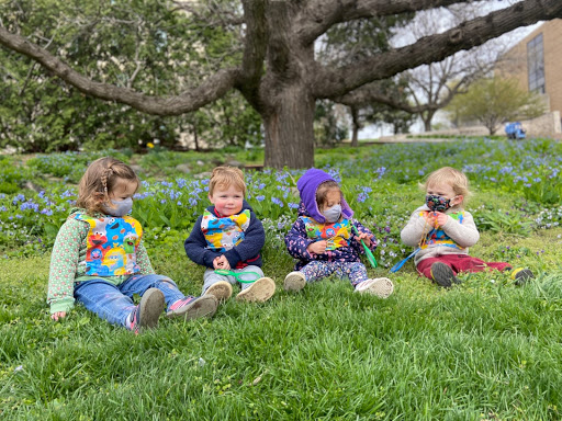 Four infant children sit in the lawn in front of the School of Human Ecology building
