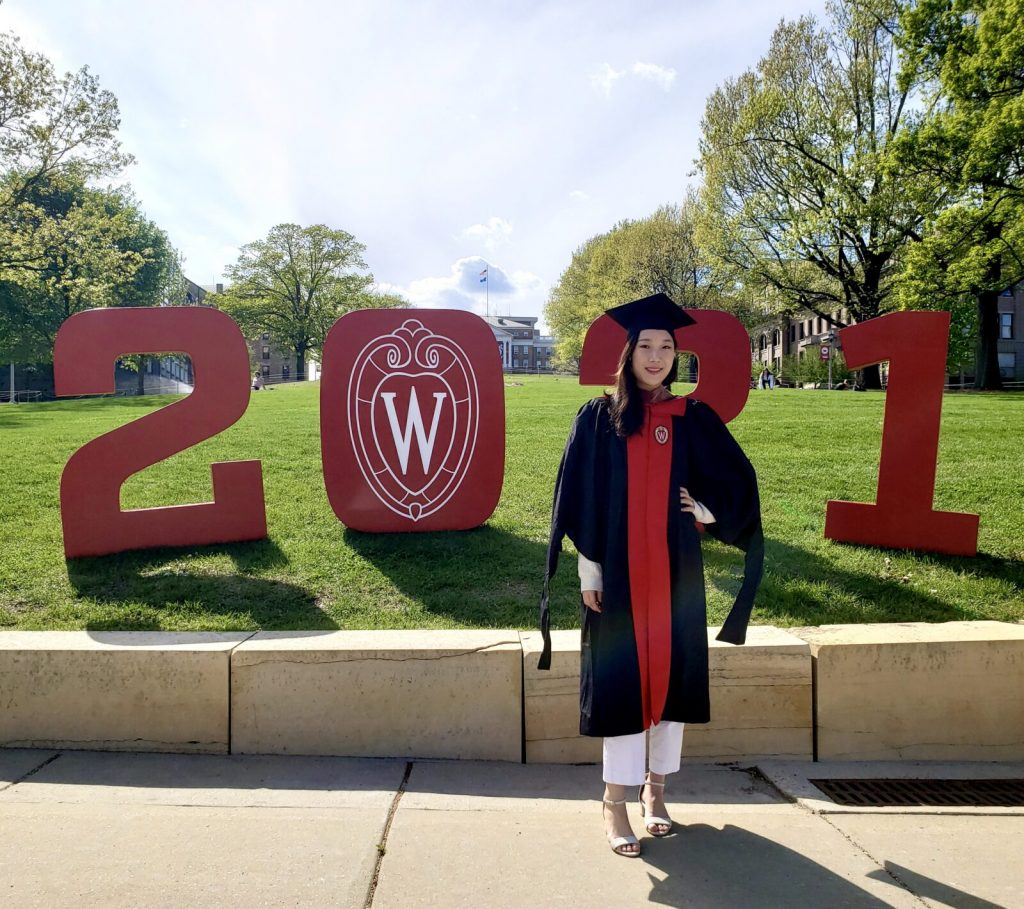 SoHE MFA graduate Han-Ah Yoo in commencement robes before a 2021 sign on Bascom Hill