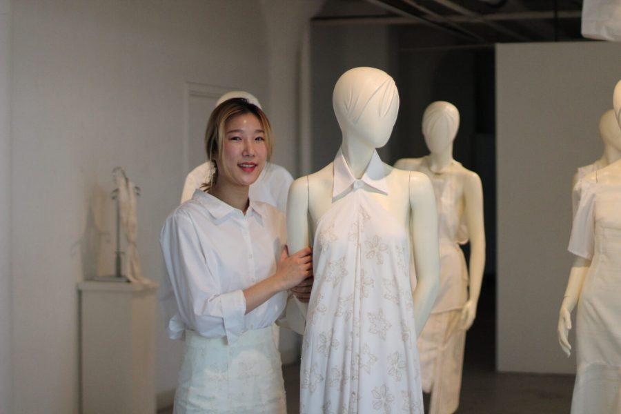SoHE MFA graduate Han-Ah Yoo stands in her exhibition space with a mannequin, May 2021