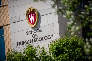 UW–Madison crest and School of Human Ecology sign on the outside of Nancy Nicholas Hall