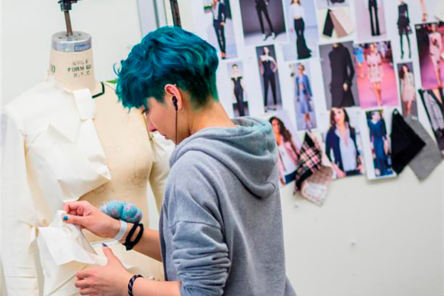 Student pins fabric onto a mannequin, photos of people and fabric samples hang in the background.