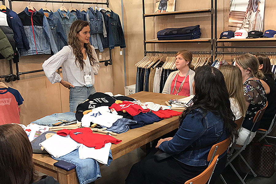 Group in a retail space with racks of clothes on the walls. Students sit around a table listening to a presenter.