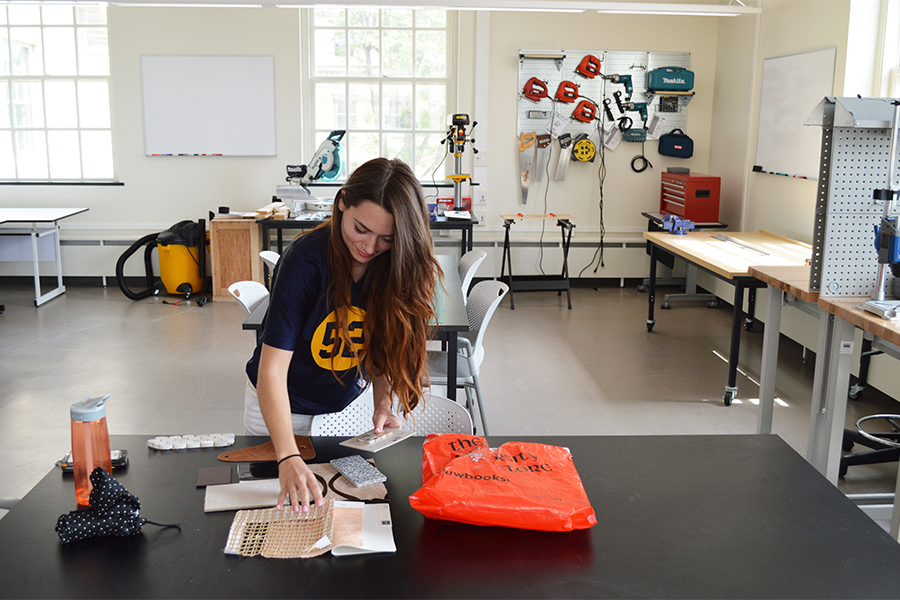 A student sorts through texture samples at a table in a workshop. There are saws and drills in the background.