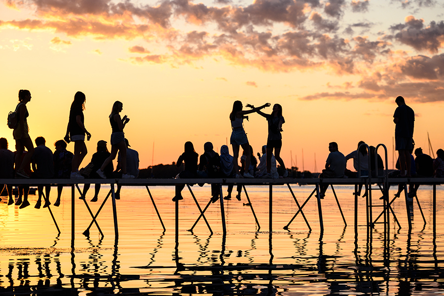 Silhouettes of people at Memorial Union Terrace pier to watch the sun set over Lake Mendota.
