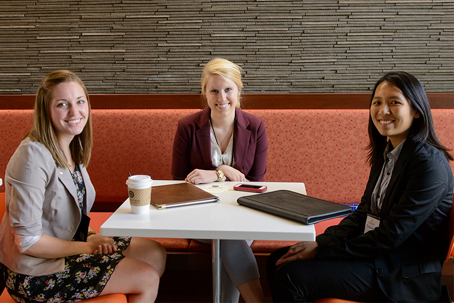 Three students dressed in business attire sit around a table smiling. There are portfolios on the table.