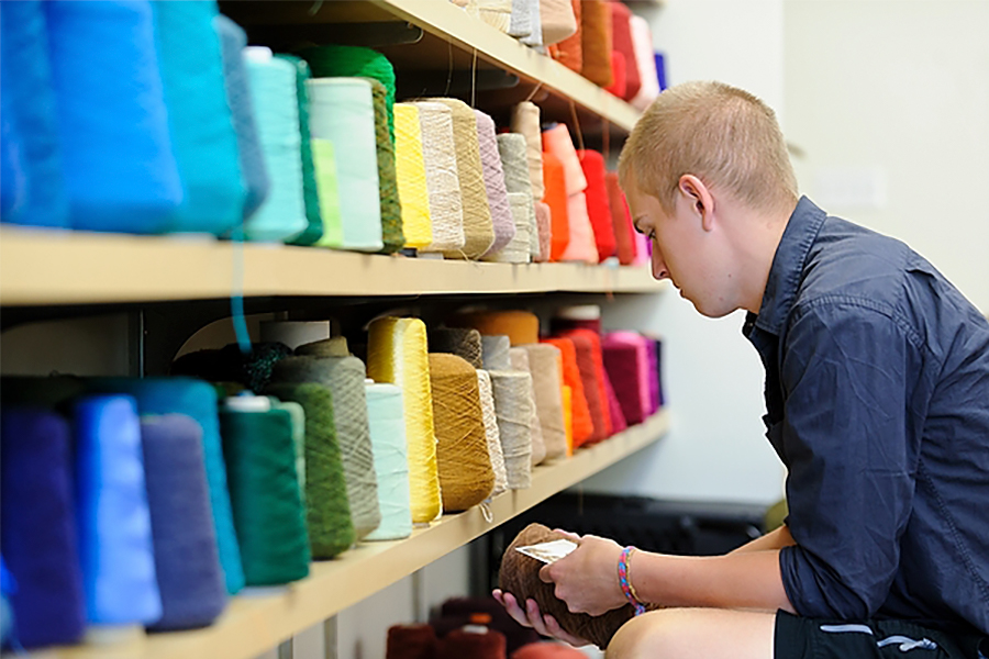 A student in front of shelves of colorful spools, holds and examines a brown spool.