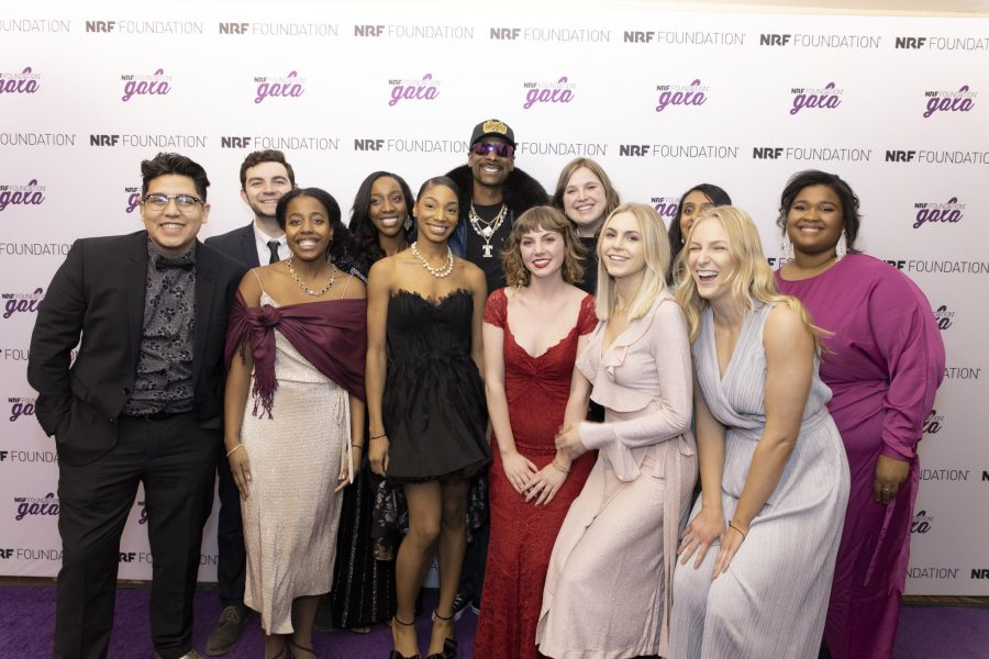 12 people, formally dressed, pose as a group in front of an NRF Foundation gala background.