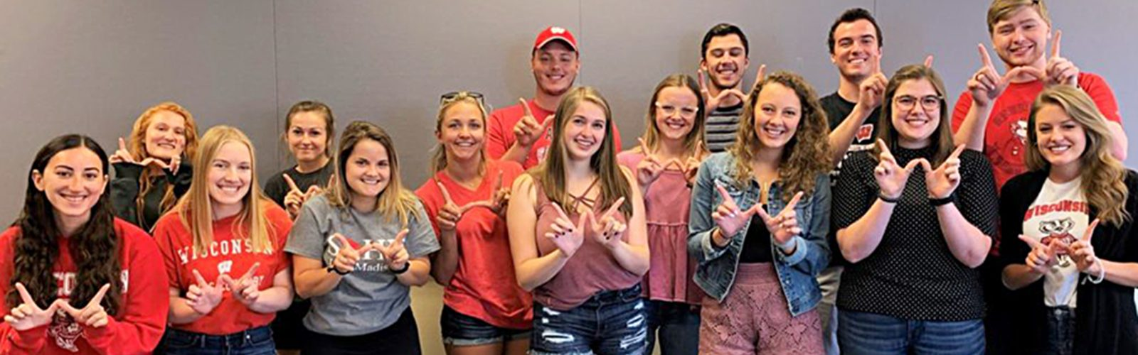 """Group of BadgerSense peer educators, wearing UW–Madison shirts, smiling and making a """"W"""" shape with their hands."""