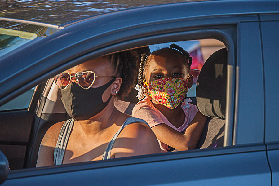 A mother and child sitting in their car with masks on.