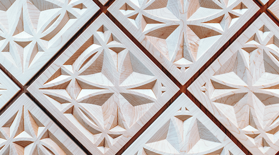 Close up of the wall in Ember Hall which is a wooden grid of diamond squares with geometric carvings inside.