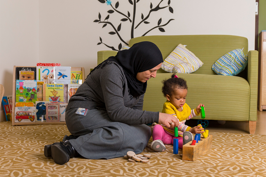 An adult sits on the floor playing blocks with a small child. Books and a couch are in the background.