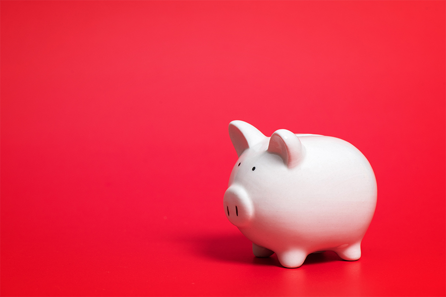 A piggy bank on a blank red background.