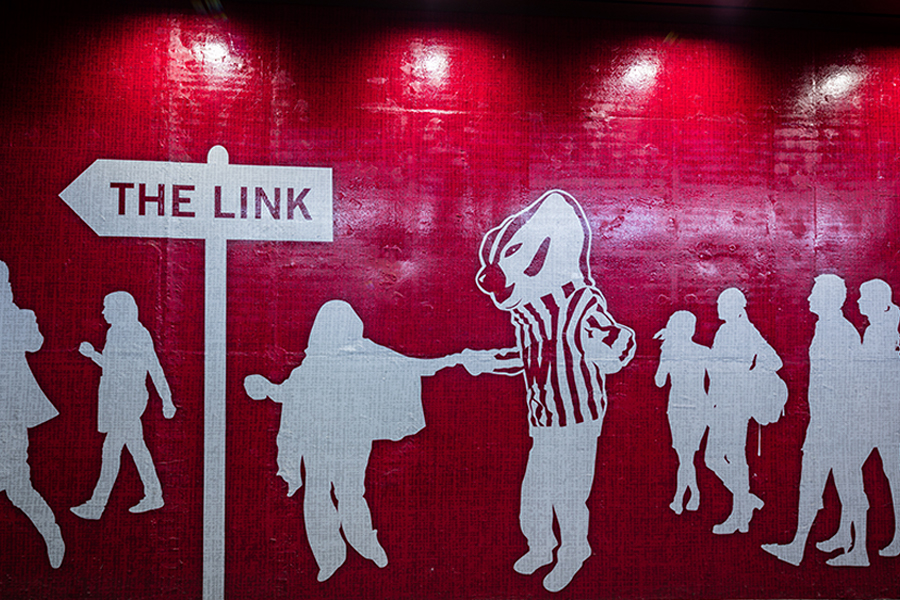 Mural of white silhouettes on a red background. Person holds hands with Bucky Badger while others walk around them.