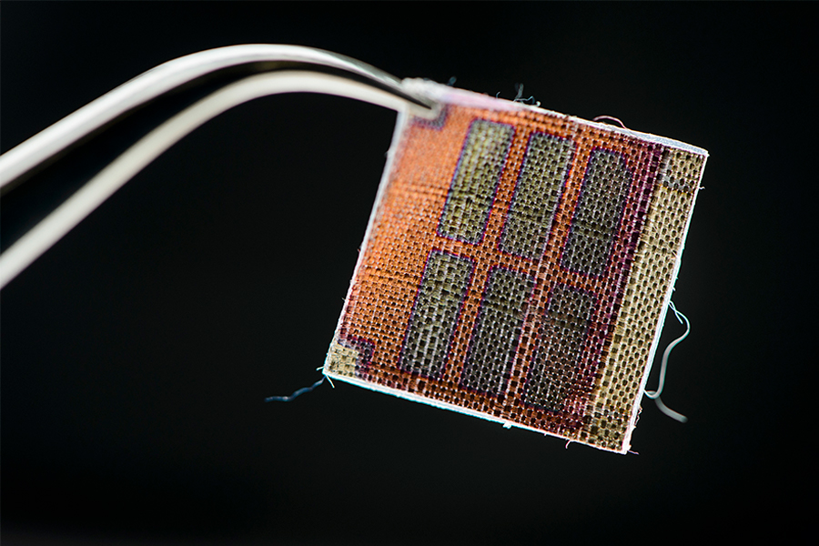 Tweezers hold a prototype for a woven solar textile. The textile is mostly orange with six green rectangles.