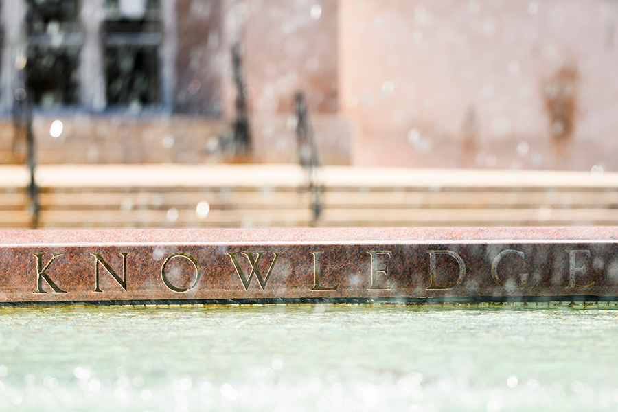 Out-of-focus water spray frames the engraved word 'knowledge' along the inner edge of the Hagenah Fountain on Library Mall.