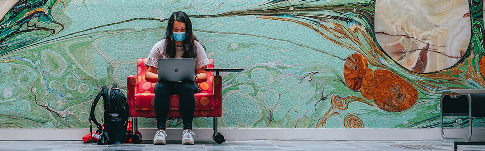 """Student sits and studies in front of the """"Threshold"""" mural in Nancy Nicholas Hall."""