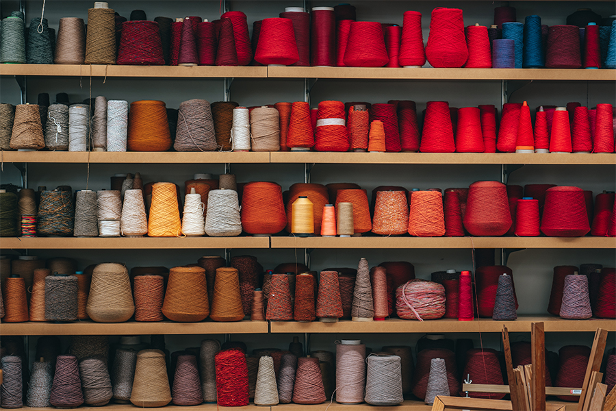 Wall of shelves with many spools of thread in all shades of the rainbow.
