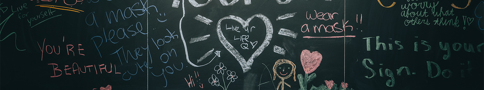 A black chalkboard with lots of colorful, positive handwritten messages. There is a large heart in the center.