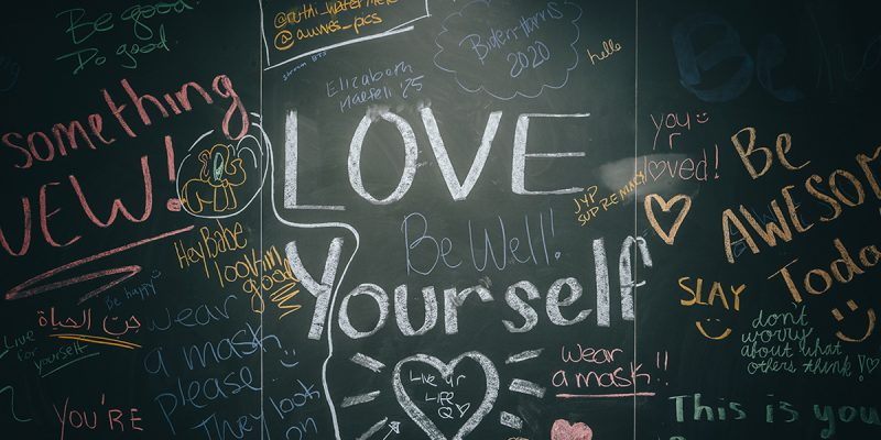A black chalkboard with lots of colorful, positive handwritten messages. Love Yourself is large and in the center.