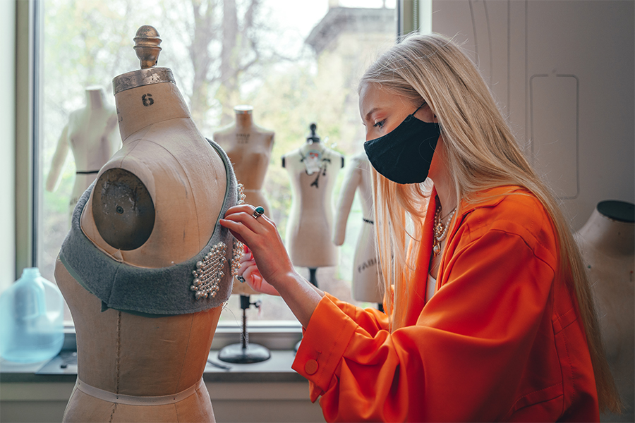 Fashion design student sews beads onto a garment that is place on a mannequin.